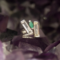 Emerald ring has a bar of clear quartz on both sides. Sterling Silver setting.